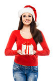 Happy woman in a Christmas hat holding a present. Young and attractive teenager girl with a Christmas present isolated on white background Stock Photography