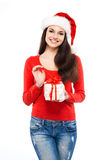 Happy woman in a Christmas hat holding a present. Young and attractive teenager girl with a Christmas present isolated on white background Royalty Free Stock Photography
