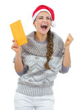 Happy woman in christmas hat with letter rejoicing Stock Image