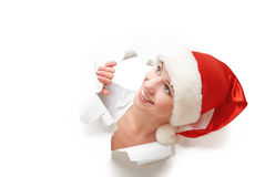 Happy woman with christmas hat peeking through a  hole torn in white paper poster Stock Photography