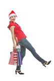 Happy woman in Christmas hat with shopping bags Stock Images
