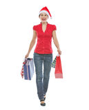 Happy woman in Christmas hat with shopping bags Royalty Free Stock Photography
