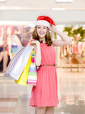 Happy woman in christmas hat with shopping bags In shopping mall Stock Photo