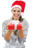 Happy woman in christmas hat showing christmas present box Royalty Free Stock Photography