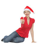 Happy woman in Christmas hat showing thumbs up Stock Photo