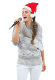 Happy woman and christmas hat singing in microphone Stock Photos