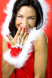 Happy woman at Christmas. Portrait of a beautiful brunette in Christmas dress smiles stock images