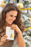 Happy woman and christmas postcard near christmas tree Royalty Free Stock Photography