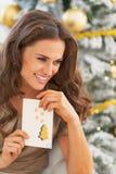Happy woman and christmas postcard near christmas tree Royalty Free Stock Photography