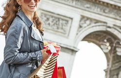 Happy woman with Christmas present near Arc de Triomphe in Paris. Stylish Christmas in Paris. Closeup on happy young woman in sunglasses with shopping bags and Stock Image