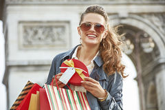 Happy woman with Christmas present near Arc de Triomphe in Paris. Stylish Christmas in Paris. Portrait of happy elegant woman in trench coat with shopping bags Royalty Free Stock Images