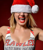 Happy woman in Christmas Santa hat screaming yelling girl on red Stock Images