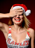 Happy woman in Christmas Santa hat smiling girl on red backgroun Royalty Free Stock Image