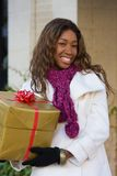 Happy Woman Christmas Shopping. Attractive young happy African American woman walking in an urban city environment and holding a Christmas gift wrapped in gold Stock Images