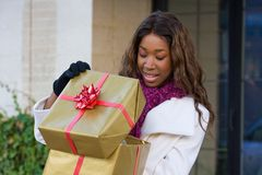 Happy Woman Christmas Shopping. Attractive young happy African American woman walking in an urban city environment and holding a Christmas gift wrapped in gold Royalty Free Stock Image