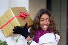 Happy Woman Christmas Shopping. Attractive young happy African American woman walking in an urban city environment and holding a Christmas gift wrapped in gold Stock Photo