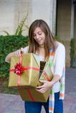 Happy Woman Christmas Shopping. Attractive young happy woman with red hair walking in an urban city environment and holding a Christmas gift wrapped in gold Stock Photography