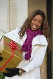 Happy Woman Christmas Shopping. Attractive young happy woman walking in an urban city environment and holding a Christmas gift wrapped in gold paper Royalty Free Stock Photo