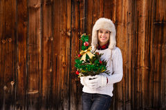 Happy woman with Christmas tree in the front of rustic wood wall Royalty Free Stock Photos