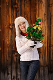 Happy woman with Christmas tree in the front of rustic wood wall Royalty Free Stock Images