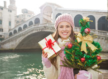 Happy woman with Christmas tree and gift box in Venice, Italy Stock Photo