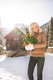 Happy woman with Christmas tree standing near mountain house Royalty Free Stock Images