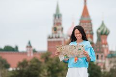 Happy young urban woman in european city. Happy woman with city map outdoors in big city on the background of famous sights in Moscow royalty free stock photography