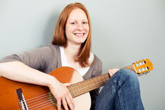 Happy woman with a classical guitar smiling at the camera Royalty Free Stock Photos