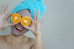Happy woman with a clay mask with biting slice of orange. royalty free stock images