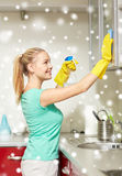 Happy woman cleaning cabinet at home kitchen. People, housework and housekeeping concept - happy woman in protective gloves cleaning cabinet with rag and royalty free stock image