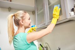 Happy woman cleaning cabinet at home kitchen. People, housework and housekeeping concept - happy woman cleaning cabinet with rag and cleanser at home kitchen Stock Photo