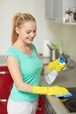 Happy woman cleaning cooker at home kitchen Stock Photo