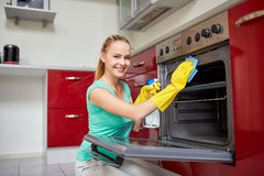 Happy woman cleaning cooker at home kitchen. People, housework and housekeeping concept - happy woman with bottle of spray cleanser cleaning oven at home kitchen Royalty Free Stock Photos