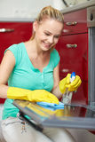 Happy woman cleaning cooker at home kitchen Royalty Free Stock Photo