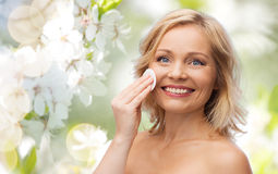 Happy woman cleaning face with cotton pad Royalty Free Stock Photo