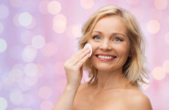 Happy woman cleaning face with cotton pad Stock Image