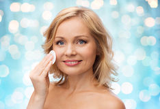 Happy woman cleaning face with cotton pad Stock Photography