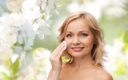 Happy woman cleaning face with cotton pad Royalty Free Stock Image