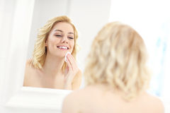 Happy woman cleaning face Stock Photography