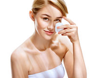 Happy woman cleaning her face with cotton pads over white background Royalty Free Stock Image