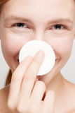 Happy woman cleaning her face with cotton pads Stock Photography