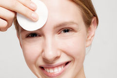 Happy woman cleaning her face with cotton pads Royalty Free Stock Image