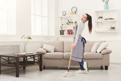 Happy woman cleaning home with mop and having fun. Happy woman cleaning home, dancing with mop and having fun, copy space. Housework, chores concept Royalty Free Stock Photos