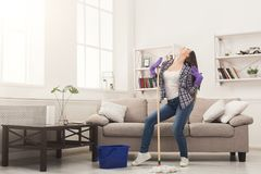 Happy woman cleaning home with mop and having fun. Happy woman cleaning home, dancing with mop and having fun, copy space. Housework, chores concept royalty free stock image