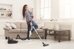 Happy woman cleaning home with vacuum cleaner stock images