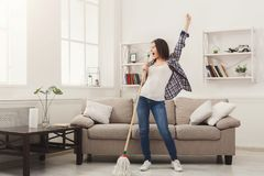 Happy woman cleaning home with mop and having fun. Happy woman cleaning home, singing at mop like at microphone and having fun, copy space. Housework, chores royalty free stock image
