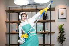 Happy woman cleaning home, singing at mop like at microphone and having fun stock images