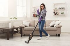 Happy woman cleaning home with vacuum cleaner royalty free stock photography
