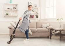 Happy woman cleaning home with vacuum cleaner royalty free stock photo