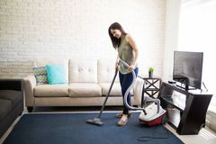Happy woman cleaning house living room. Cheerful young housewife cleaning house area with vacuum cleaner Stock Photography